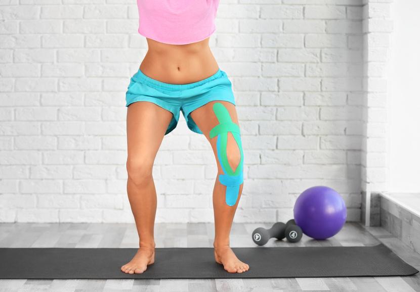 Frau mit getapeten Knie führt Sportübungen aus