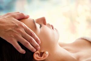 Osteopathie Herne: Osteopath hält Kopf einer Frau